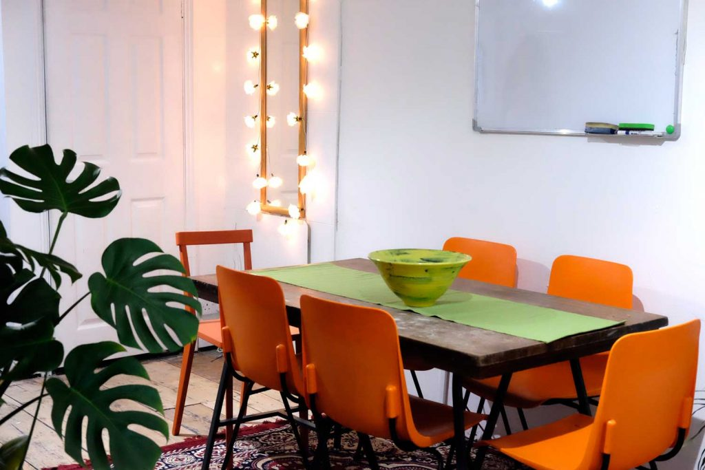 Mirror with fairy lights and meeting table and whiteboard at Social Streets Co-Lab on Roman Road